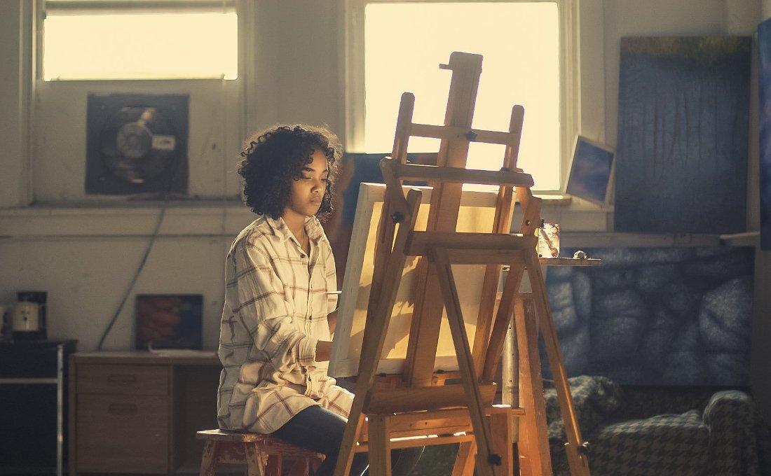 Pintora en su taller pintando un cuadro en un caballete.