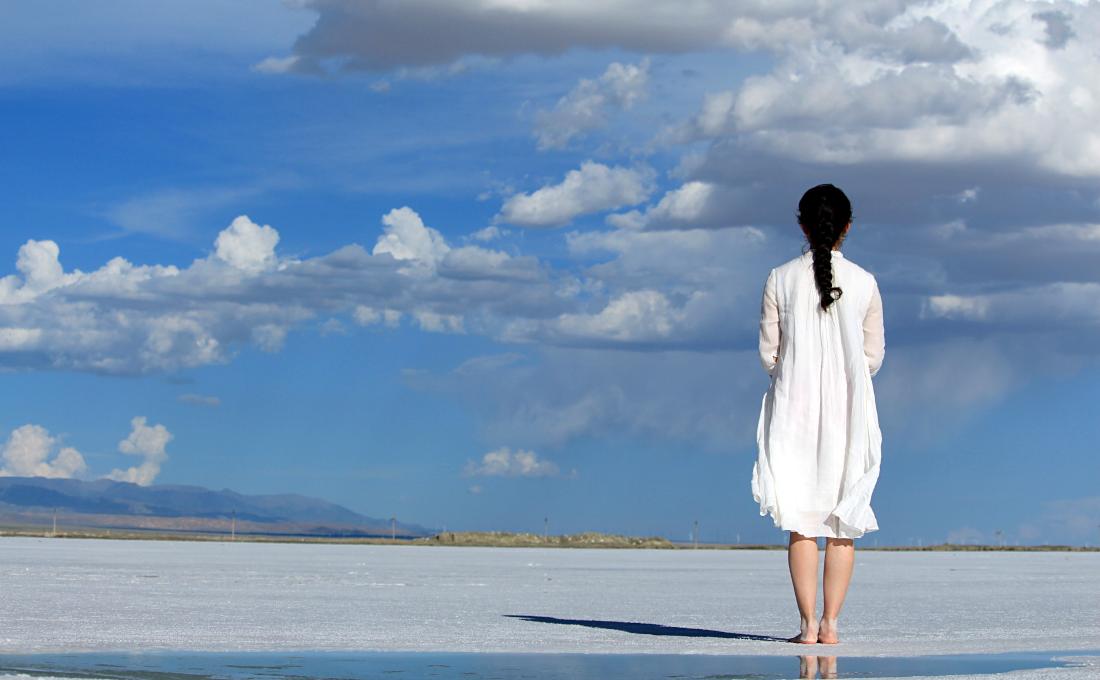 Mujer de espalda mirando el horizonte.