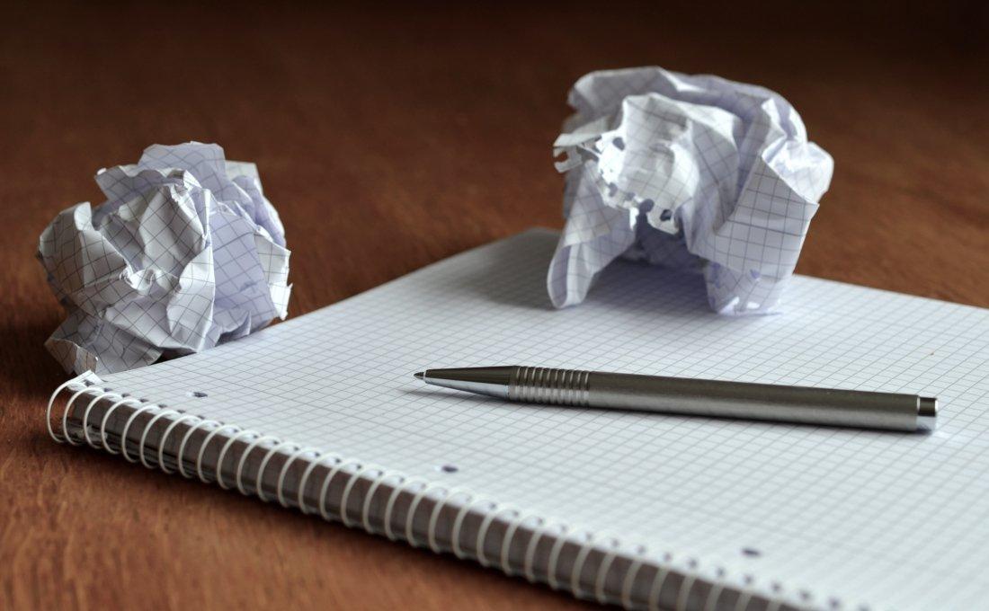 Bloc con papeles arrancados y arrugados.