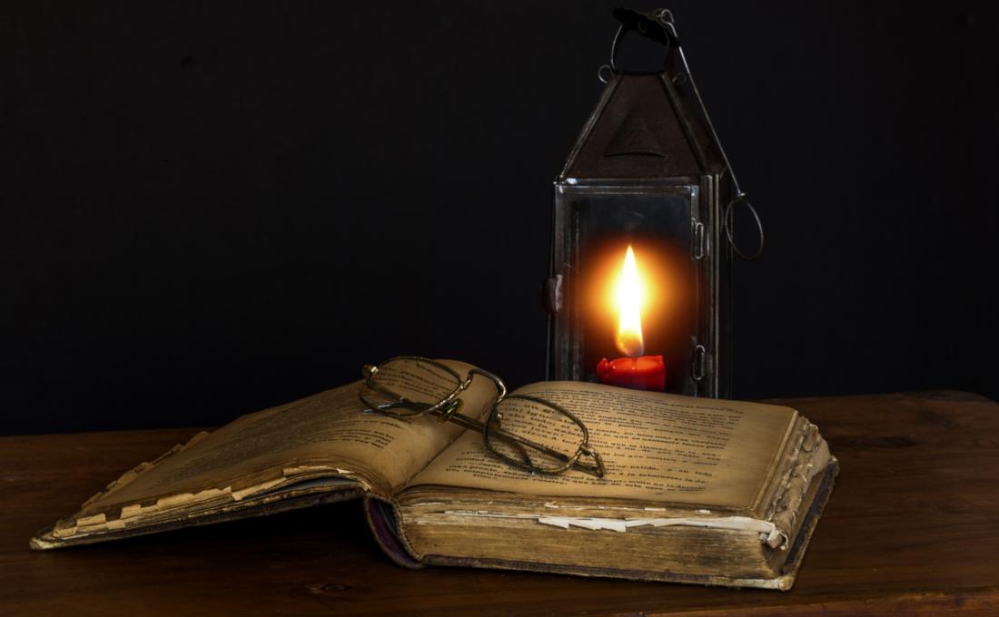 Lápara antigua con un cirio que ilumina un libro.